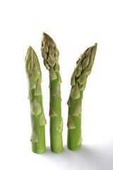 three asparagus spears standing over white backgrond with light