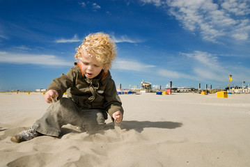 cute boy playing with sand