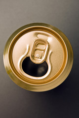 aluminum  can of gold color costs on a grey background