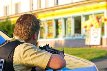 Polizei mit Maschinenpistole im Anschlag