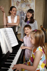 A group of young people playing piano and singing