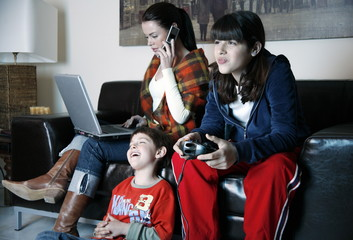 Mother works on laptop while children play video game