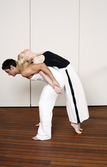 Partners practicing flexibility in yoga and Capoeira programs