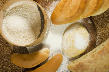 Various types of bakery with flour and dough on wheat background
