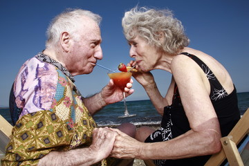 Senior couple with cocktail on beach