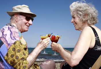 Senior couple with cocktails on beach