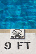 """no diving"" sign on a pool deck"