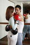 Young man and woman embracing in kickboxing class