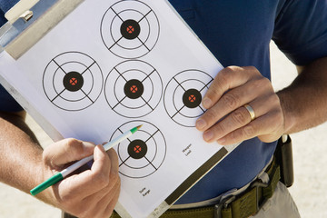 Instructor holding clipboard with target diagram, mid section