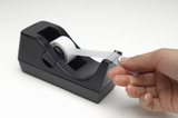 Person taking piece of tape from dispenser, close-up of hand