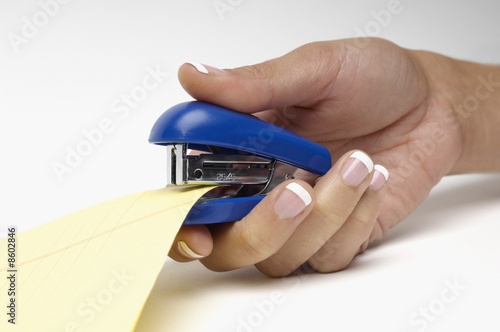 Woman using stapler, close-up of hand