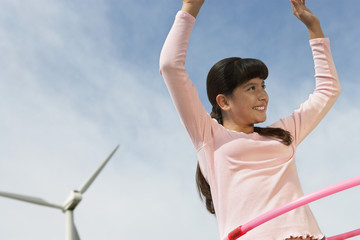 Girl 7-9 playing with hula hoop at wind farm