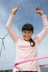 Girl 7-9 playing with hula hoop at wind farm, portrait
