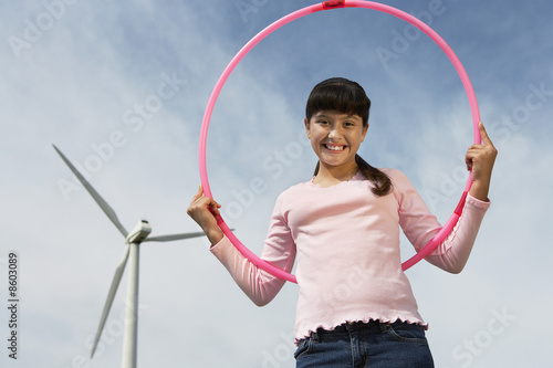 Girl 7-9 holding hula hoop at wind farm, portrait