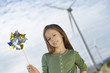 Girl 5-6 holding toy windmill at wind farm, portrait