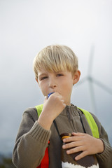 Boy 7-9 blowing toy whistle at wind farm, portrait