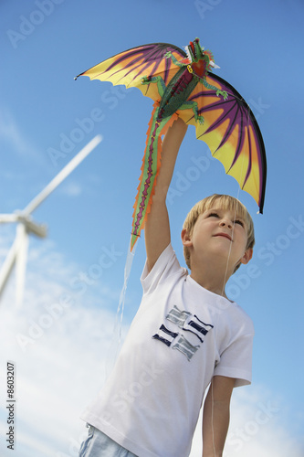 Boy 7-9 playing with kite at wind farm