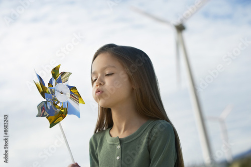 Girl 5-6 blowing toy windmill at wind farm