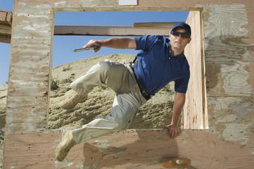 Man with hand gun jumping obstacle at firing range