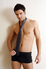 Bare chested young man posing with shorts and tie