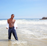 Handsome African American Man Removing His Shirt in the Ocean poster