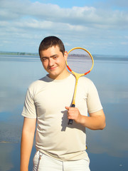 Young man with a racket for a badminton on the riverside.