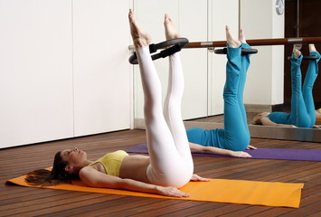 Two young women performing a pilates exercise