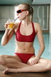 Young woman  drinking juice at spa pool