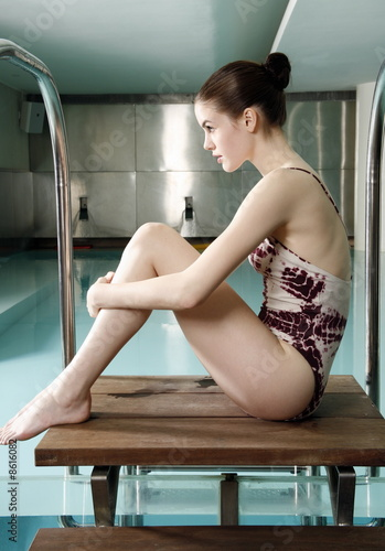 Young woman  sitting next  to spa pool