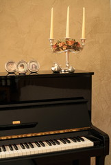 Piano decorated with photos and candelabra