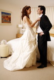 Bride undressing groom in hotel room