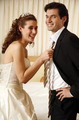 Bride pulling groom's tie off in hotel room