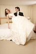 Groom holding bride in his arms in hotel room