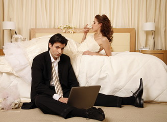 Bride drinking and groom on laptop