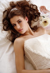 Bride lying down on wedding bed
