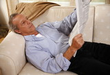 Mature man reading newspaper on couch