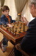 Mature man and little boy playing chess