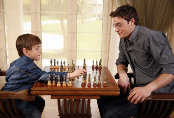 Young man and little boy playing chess