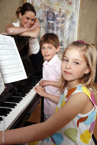 Mother looking at her children playing piano