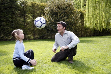 Man teaching girl to play soccer