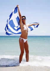 Young woman on beach holding up Greek flag