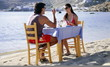 Young couple eating at seaside restaurant