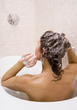 Young woman takes a bath with shampoo poster