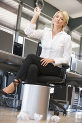Businesswoman in office space throwing garbage in bin