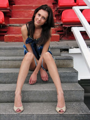 Sexy girl with long legs is sitting on the stairway.