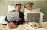 Mature couple working in bed