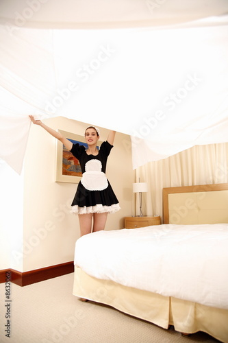 Hotel maid making the bed