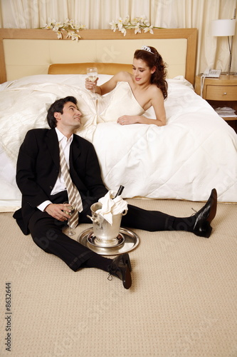 Bride and groom toasting in hotel room