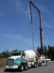 Mixing truck discharging concrete into a truck-mounted pump.