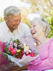 Husband giving wife flowers outdoors smiling